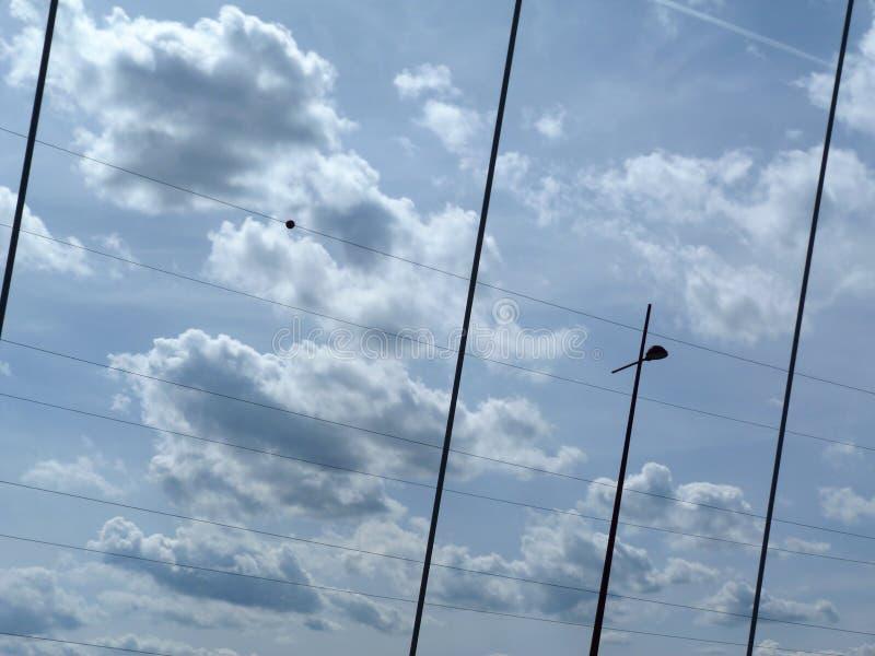 Cloudscape con los cables del puente y los cables eléctricos de alto voltaje fotos de archivo