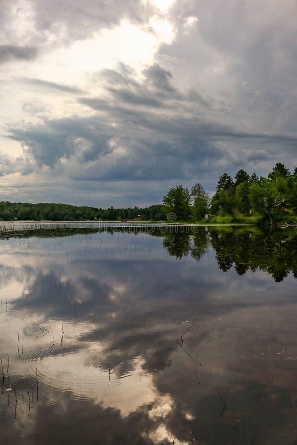 Cloudscape dramático sobre a água de rios com árvores imagem de stock