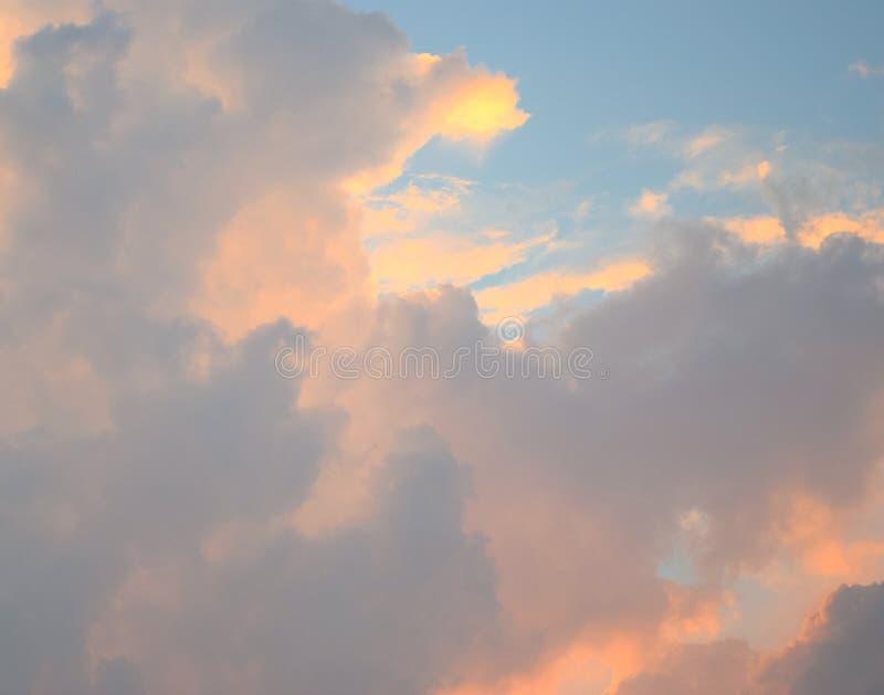 Cloudscape - fond naturel abstrait - modèle des cumulonimbus oranges et foncés jaunâtres en ciel bleu photographie stock libre de droits