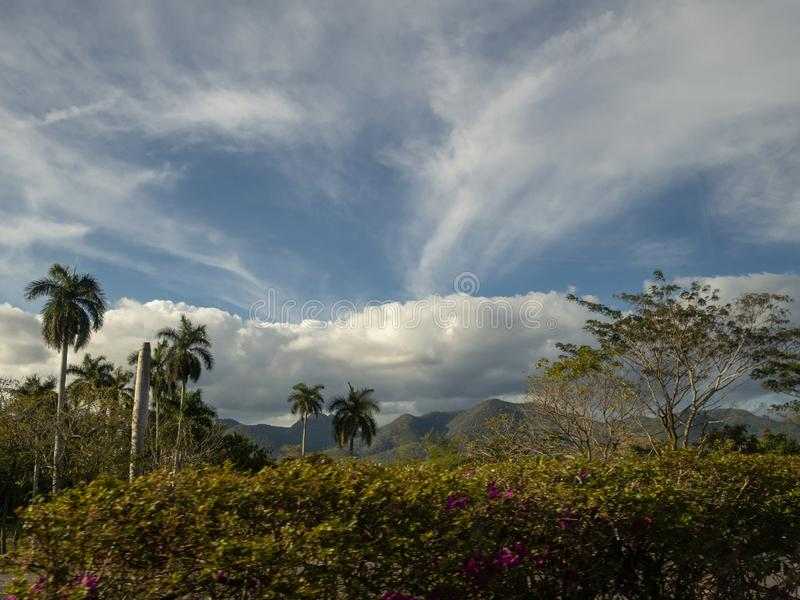 Cloudscape over the hills and vegetation of Cuba. Blue sky and dramatic clouds over the landscape of Cuba with palm trees, cloudscape, trip, nature, road, lush royalty free stock photography