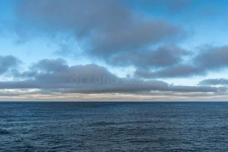 Cloudscape over Tasman Sea in morning, Tasmania Australia. Tasman Sea, Australia - March 20, 2017: Lower third of photo is blue sea water with low hanging brown stock photos