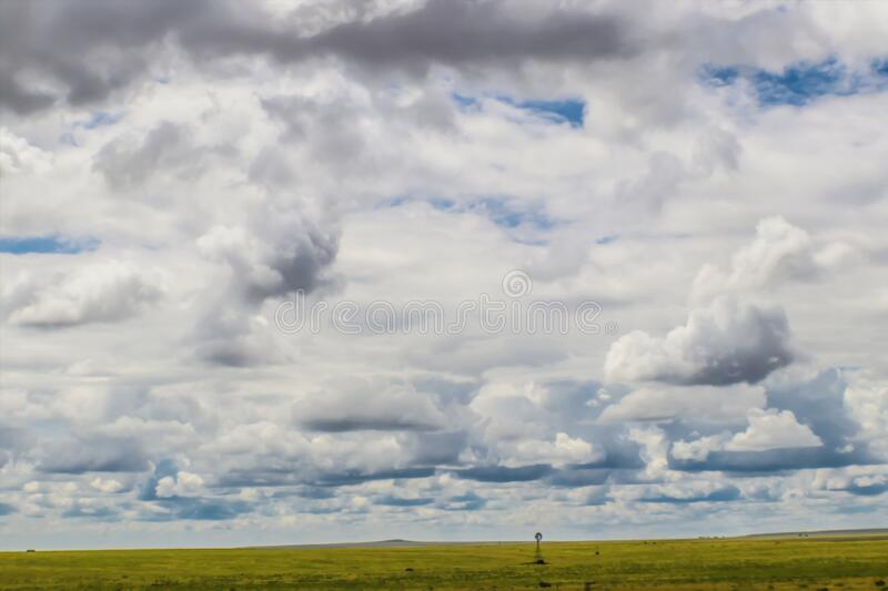 Cloudscape on the plains with windmill in the distance - Big sky country royalty free stock photos