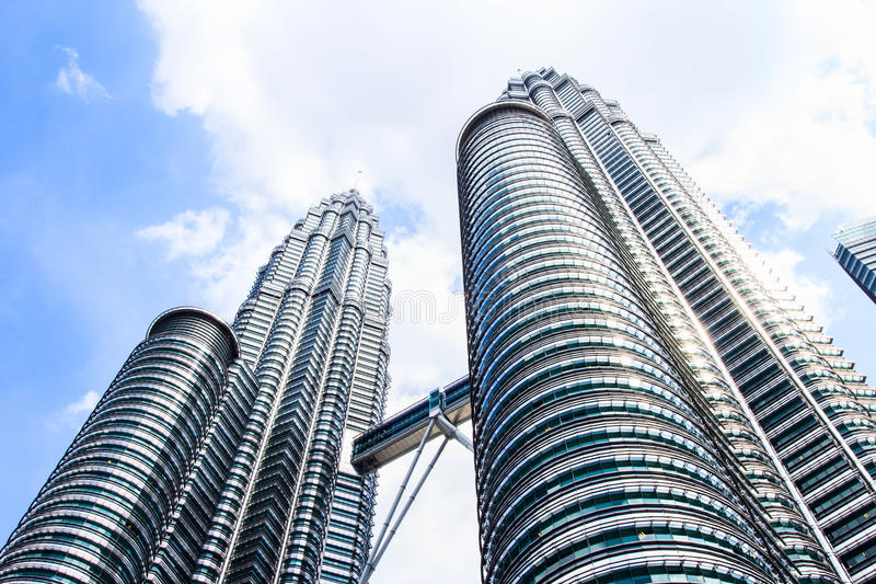 Cloudscape view of the Petronas Twin Towers at KLCC City Center. The most popular tourist destination in Malaysian capital. KUALA LUMPUR, MALAYSIA - FEB10, 2015 royalty free stock photography