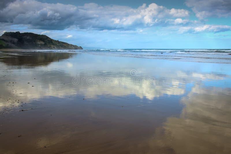 Cloudscapes refletiu na areia molhada na praia de Makorori, Gisborne, Nova Zelândia fotos de stock royalty free