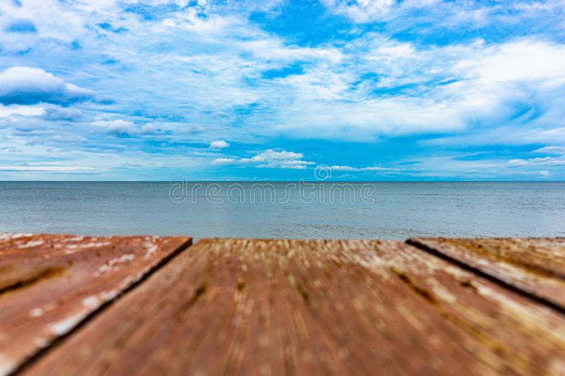 Blue sky and sea background and blurred wooden board foreground. The cloudy blue sky and sea background and blurred wooden board foreground royalty free stock images