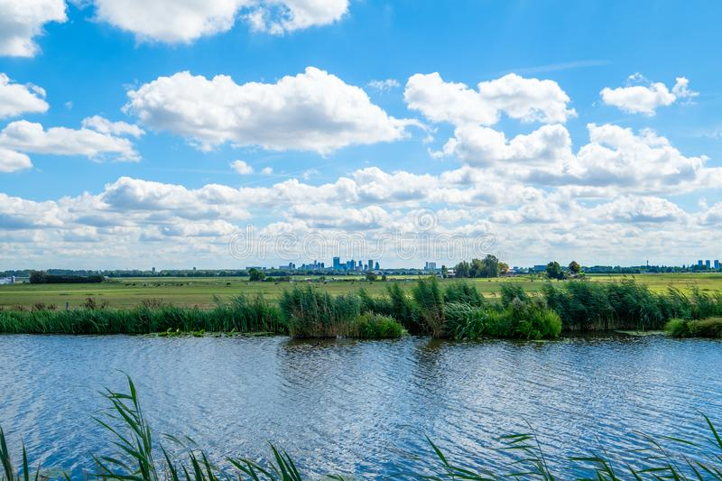 Cloudy blue sky and skyline of Rotterdam city seen from the polder. Cloudy blue sky and skyline of Rotterdam city seen from a polder. Polder canal close to royalty free stock images