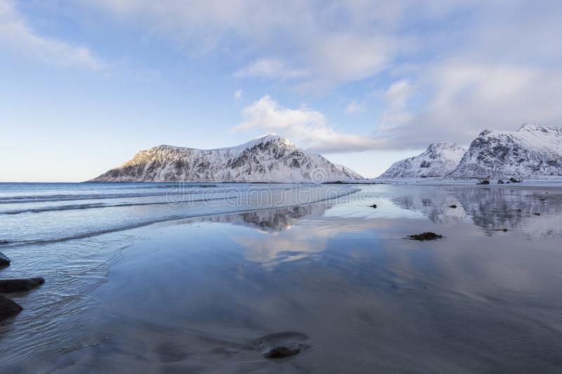 Cloudy blue sky and snowy mountain reflections on Skagsanden beach at Flakstad, Lofoten. Cloudy blue sky and snowy winter mountain reflections on Skagsanden royalty free stock images