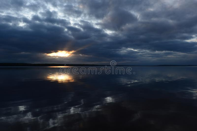 Cloudy blue sky at sunset in a bright beautiful glow of the sun`s rays from the heavenly  sunlight clouds clearance reflects in stock photo