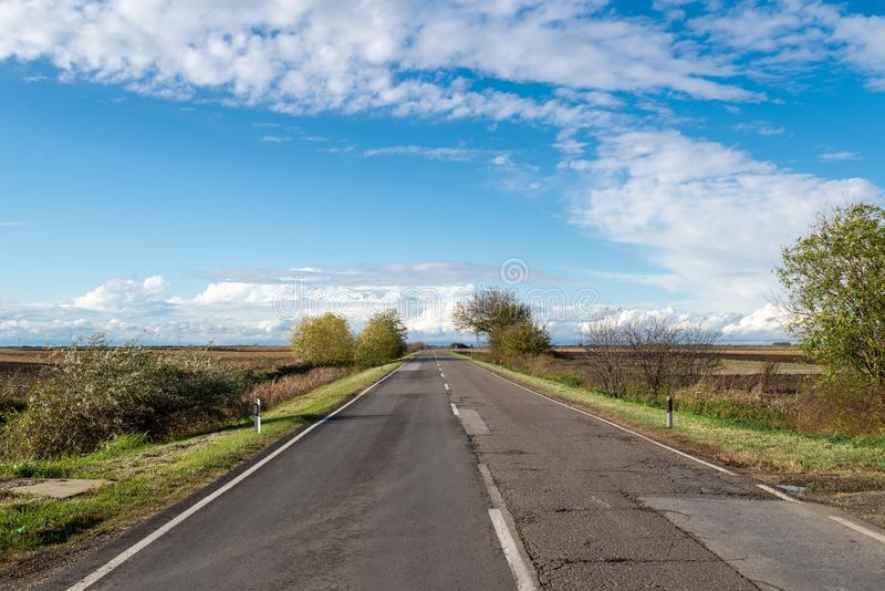 Cloudy country repaired highway/road in bad condition and blue cloudy sky. Green and yellow/orange fields, sunny landscape royalty free stock photos