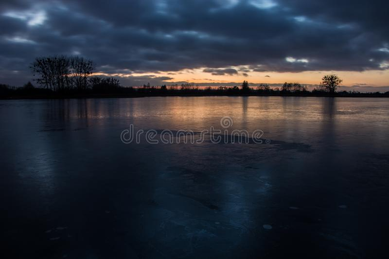 Cloudy dark clouds after sunset on a frozen lake and reflecting light on the ice royalty free stock images