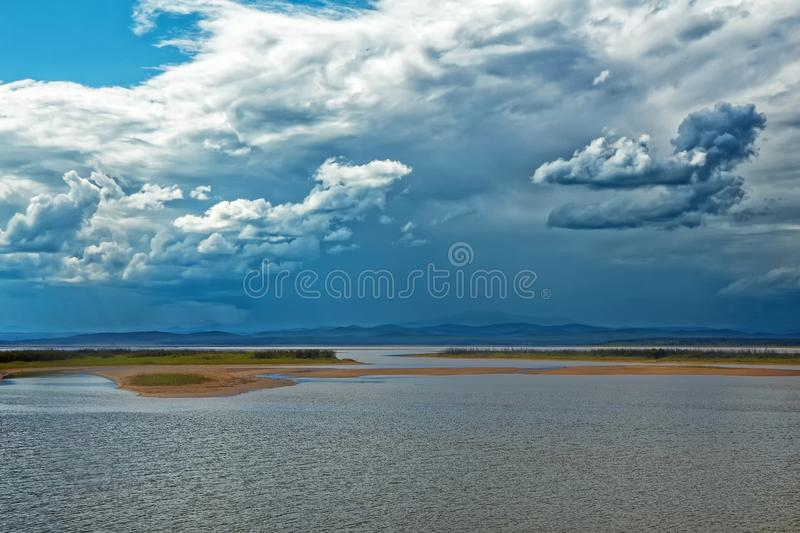 A cloudy dark sky over the lake royalty free stock photography