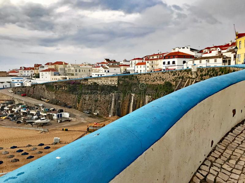 Cloudy day in Ericeira, Portugal. The blue painted wall brightens cloudy day at Fisherman`s Beach in Ericiera, Portugal stock photography