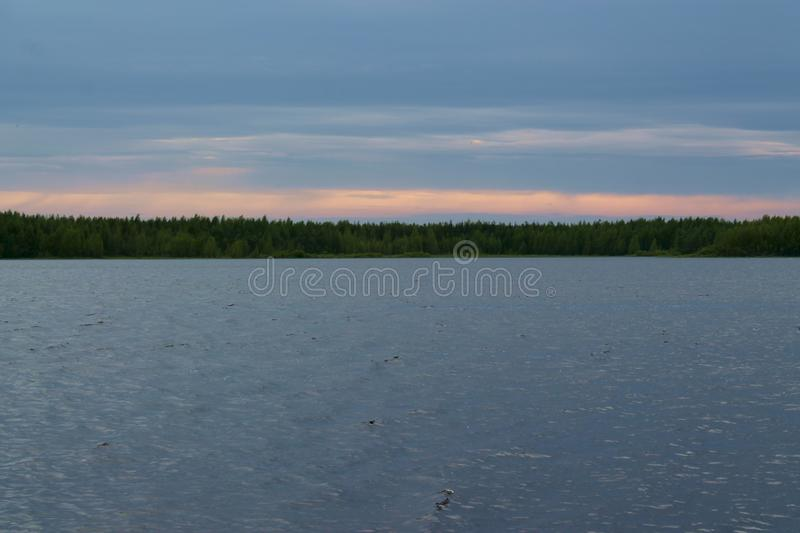 Cloudy day on the lake. A Cloudy landscape of the lake in Finland. Forest on the horizon stock photography