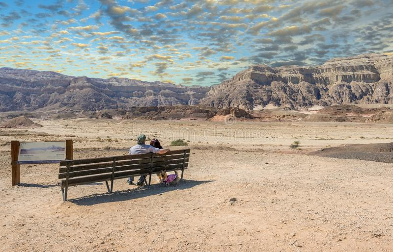 Cloudy day in Timna geological park, couple of seniors are looking at mountains royalty free stock photography
