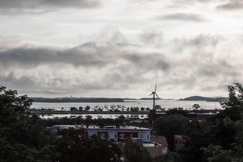 Cloudy daybreak with water reflections and windmill, Dorchester Bay Basin, Boston royalty free stock photography