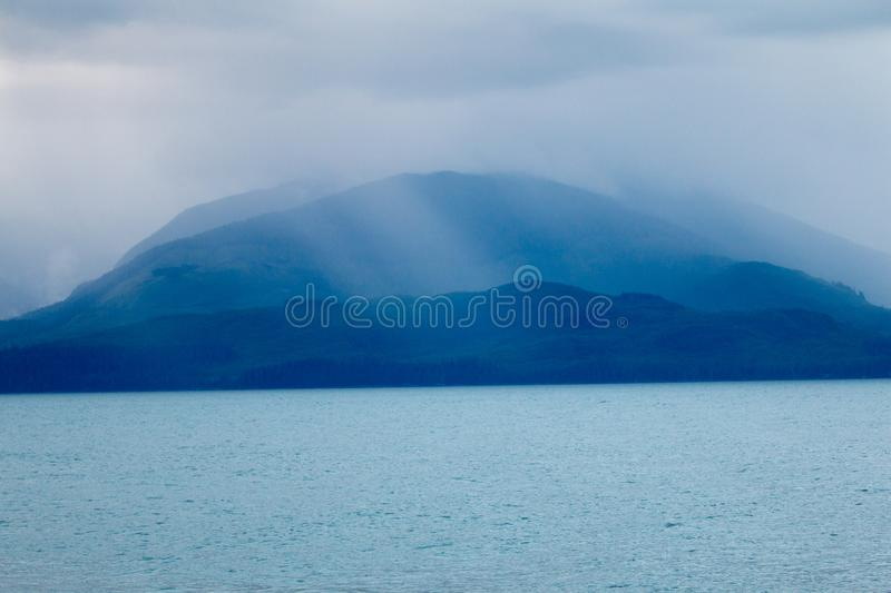 Cloudy dreamlike island. In Alaska Ray& x27;s of sunlight through clouds and fog make the blue forests and ocean look like a fantasy, rays stock photography