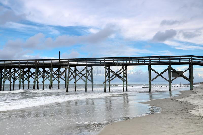Cloudy evening at Atlantic ocean beach. Atlantic ocean waves, scenic view with the wooden pier at Pawleys Island, South Carolina, Myrtle Beach area, USA stock photo