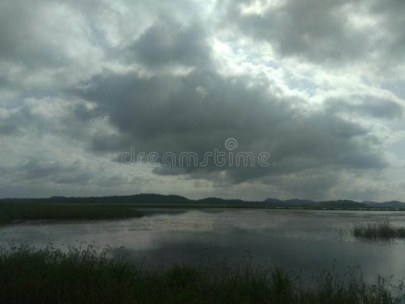 Cloudy evening with a lake. This is a beautiful picture of cloudy evening in nagpur with a lake and grasses stock photos