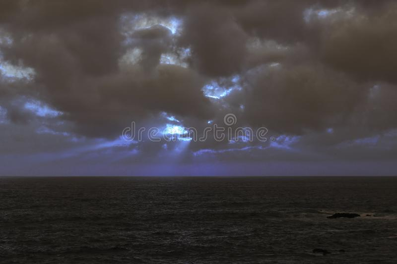 Cloudy full moon night at sea stock photography