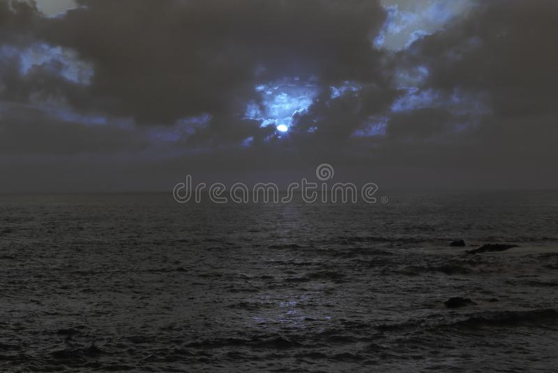 Cloudy full moon night at sea royalty free stock photography