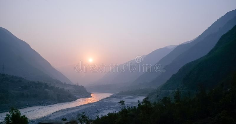 Cloudy landscape view of sunset over Indus river and layers of Karakoram mountain range, Pakistan royalty free stock photos