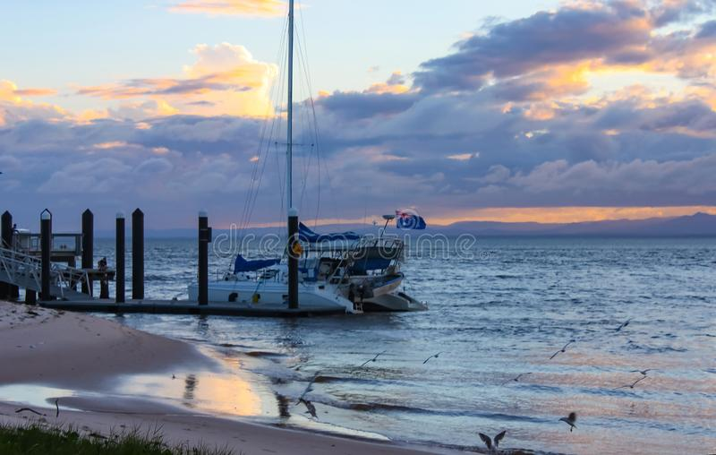 Cloudy late sunset over the ocean with catamaran sailboat with B royalty free stock image