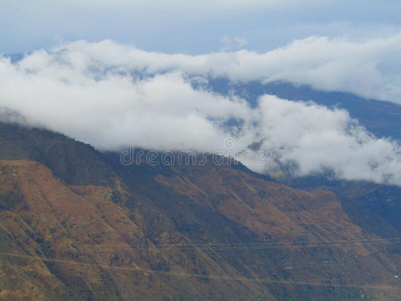 Cloudy Mountain top in india. Beautiful White Clouds covered the brown  mountain top in Munnar Kerala india stock image