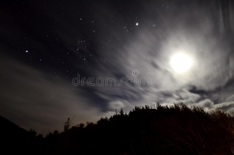 Cloudy night with stars and moon royalty free stock image