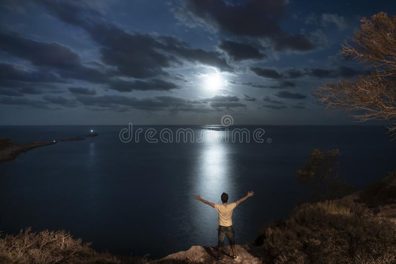 A man with open arms in a seascape bright full moon stock photo