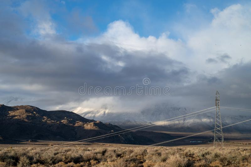 Cloudy November sky over snowy mountains and hills, electrical power lines, towers, desert Eastern Sierra Nevadas, California, USA. Morning sunlight on hills royalty free stock photography
