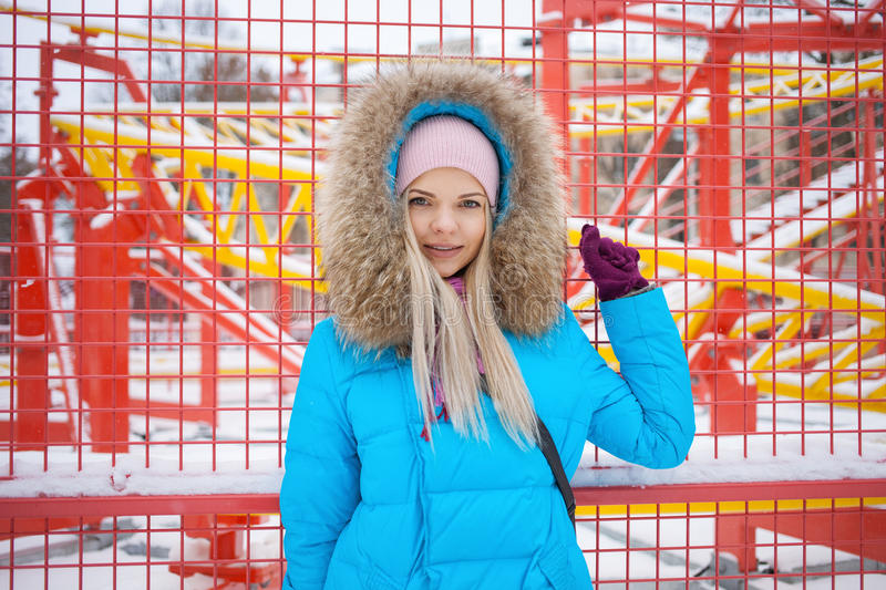 Cloudy outdoor winter portrait of young happy adorable woman in bright cyan coat posing in winter city park against bright red and. Yellow blurred carousels stock images