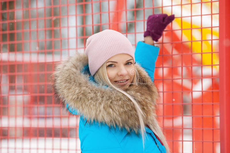 Cloudy outdoor winter portrait of young happy adorable woman in bright cyan coat posing in winter city park against bright red and royalty free stock image