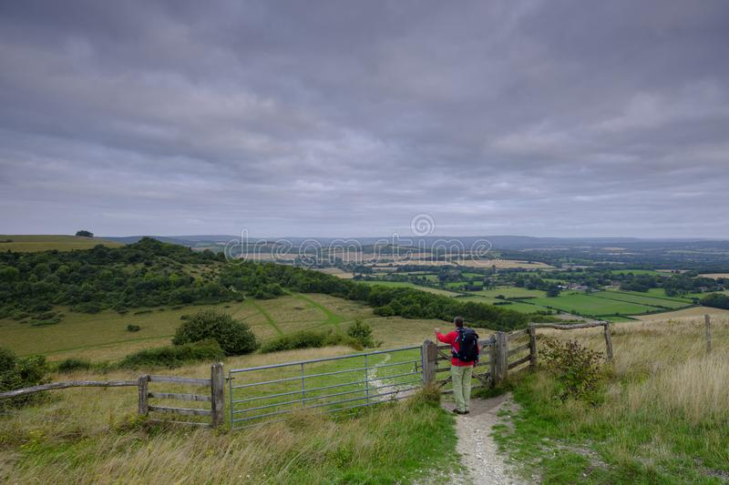 Cloudy overcast summer sunrise over the South Downs Way footpath from A middle aged male walker with backpack admiring the view stock photo