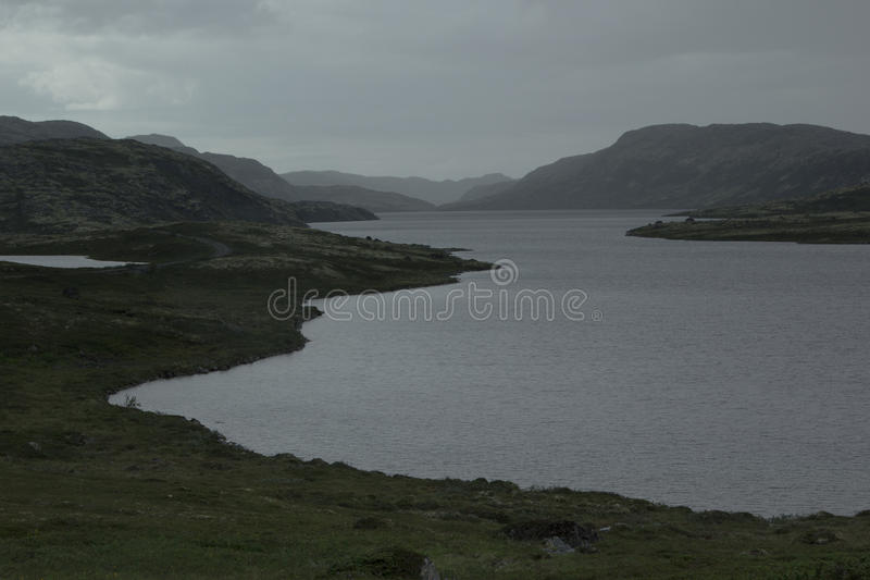 Cloudy rainy dreary landscape with views of the lake and mountains. royalty free stock images