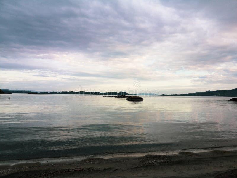Cloudy skies in the afternoon. Rock, finny, nature, background, sunset, calm, seas, beach, seashore, kvitevik royalty free stock image