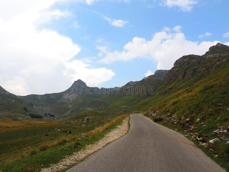 Cloudy sky over mountain Durmitor and wild flowers. Mountain road under the cloudy sky stock photography