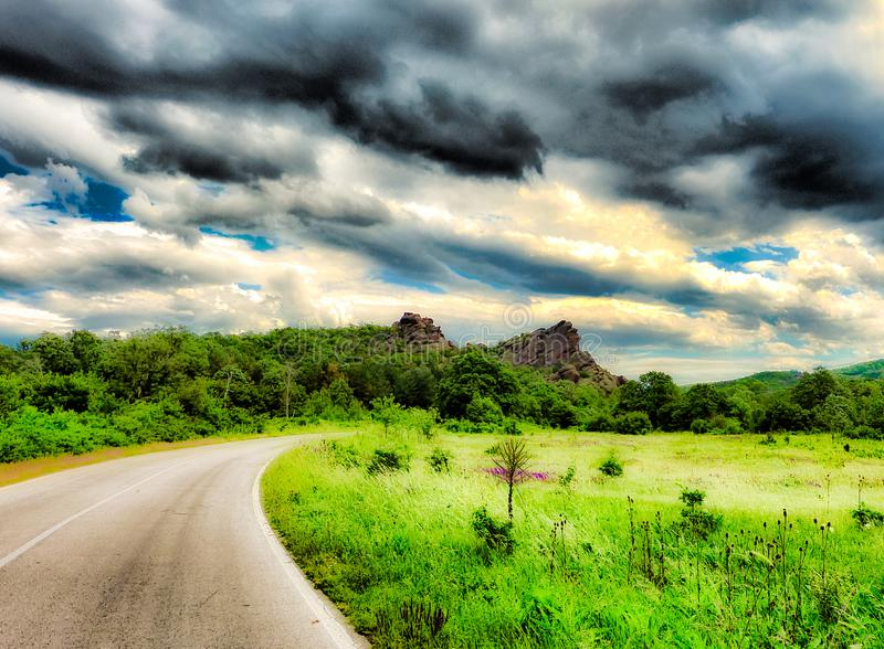 Cloudy Sky over Rocky Hill among Green Forest, Meadow, and Road royalty free stock images