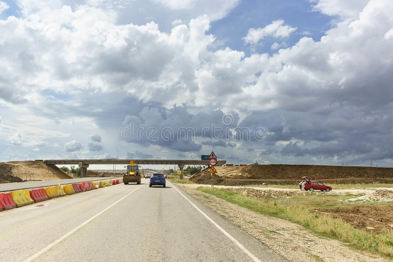 Cloudy sky over the two-level junction of the new Tavrida highway under construction. The new section of the road is fenced with m. Tavrida highway, Crimea royalty free stock photo