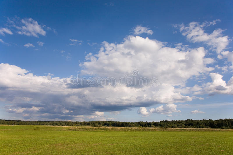 Cloudy sky and sun over cultivated meadows stock image