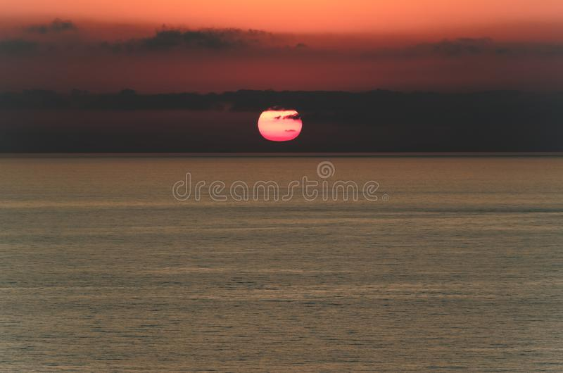 Cloudy sky at sunset above the tyrrhenian sea. The sun is behind of dark clouds over horizon stock photo