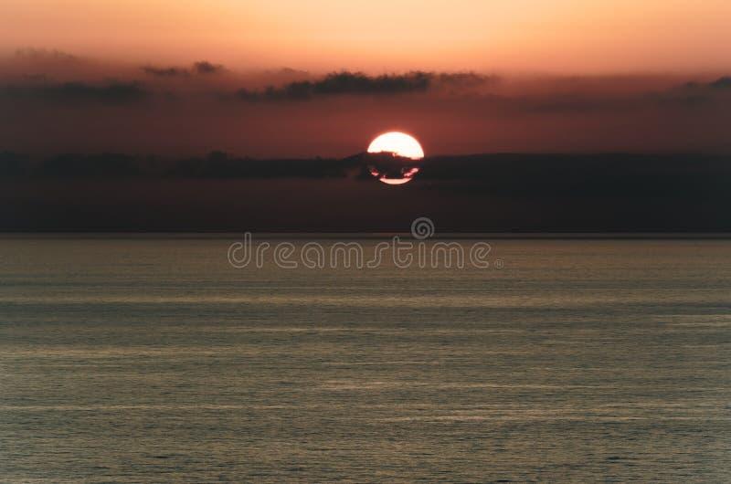 Cloudy sky at sunset above the tyrrhenian sea. Sun behind dark clouds. View from Riaci beach near Tropea, Italy stock photography