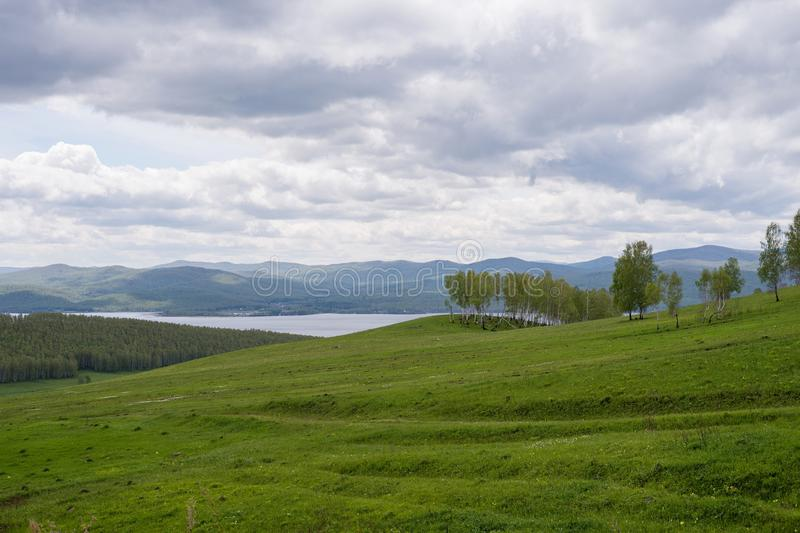A cloudy spring landscape with a blooming hill and a lake in the distance. royalty free stock photography