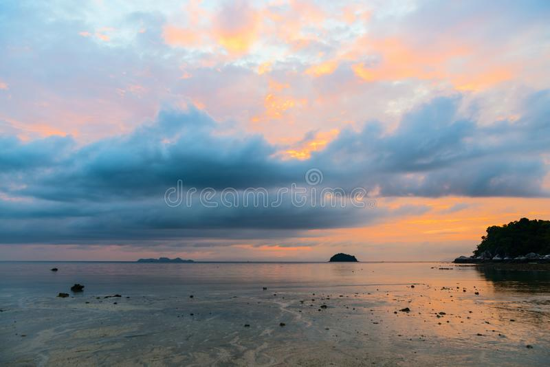 Cloudy sunrise above the sea and island. Cloudy bright orange sunrise above the calm sea and island stock images