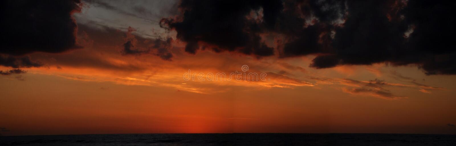 Cloudy Sunset in Cefalu, Sicily. Ornage sunset on a beach of sicily stock photography