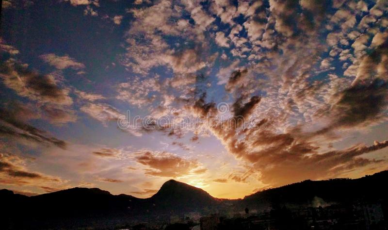 Cloudy sunset skies over a mountain royalty free stock image