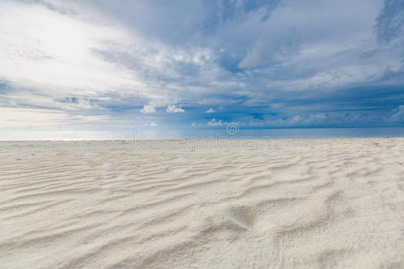 Cloudy tropical landscape. Beach view with sand and sea under overcast sky. Beach landscape of empty tropical paradise. White sand with sand waves and blue calm stock photos