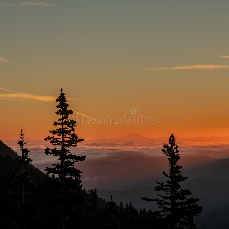 Cloudy Valley with orange Sunrise over Mount Baker. In Washington wilderness royalty free stock images