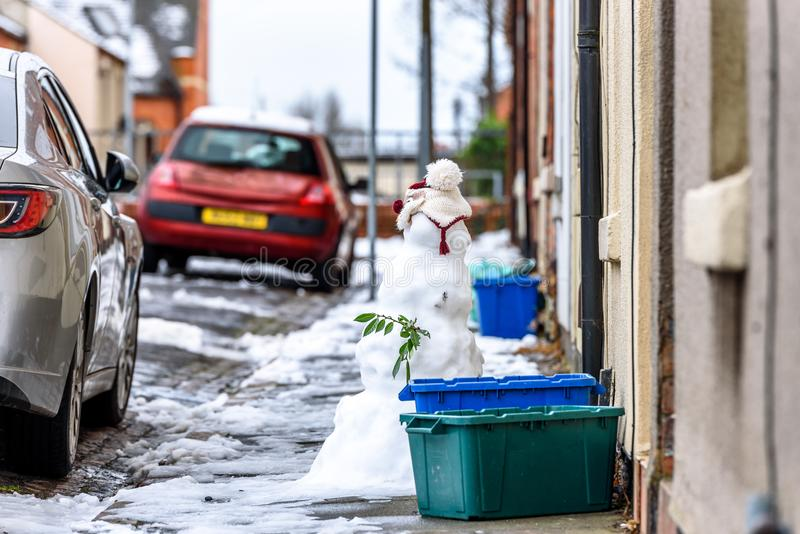 Cloudy winter day view of homemade snowman on typical british road footpath next to empty recycling bin boxes stock image