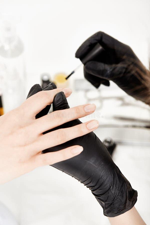 Clouez l'artiste dans les gants tenant la main de femme appliquant clairement le poli photographie stock