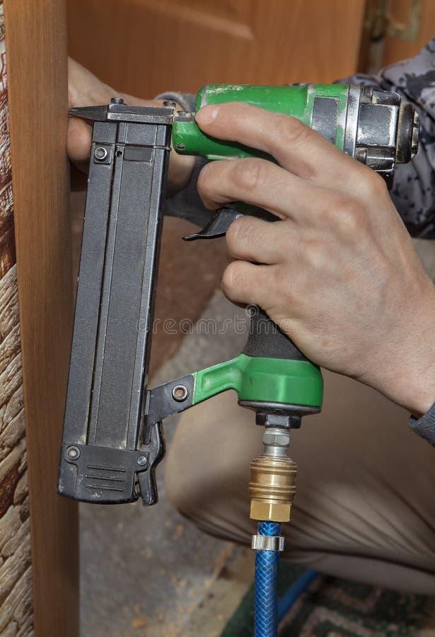 Clouez l'enveloppe principale au jambage, utilisant l'arme à feu de clou, pointe de pousse image libre de droits